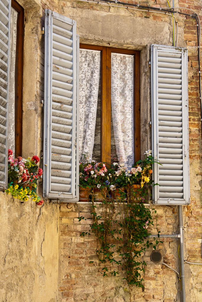 Italian window with flowers in Tuscany